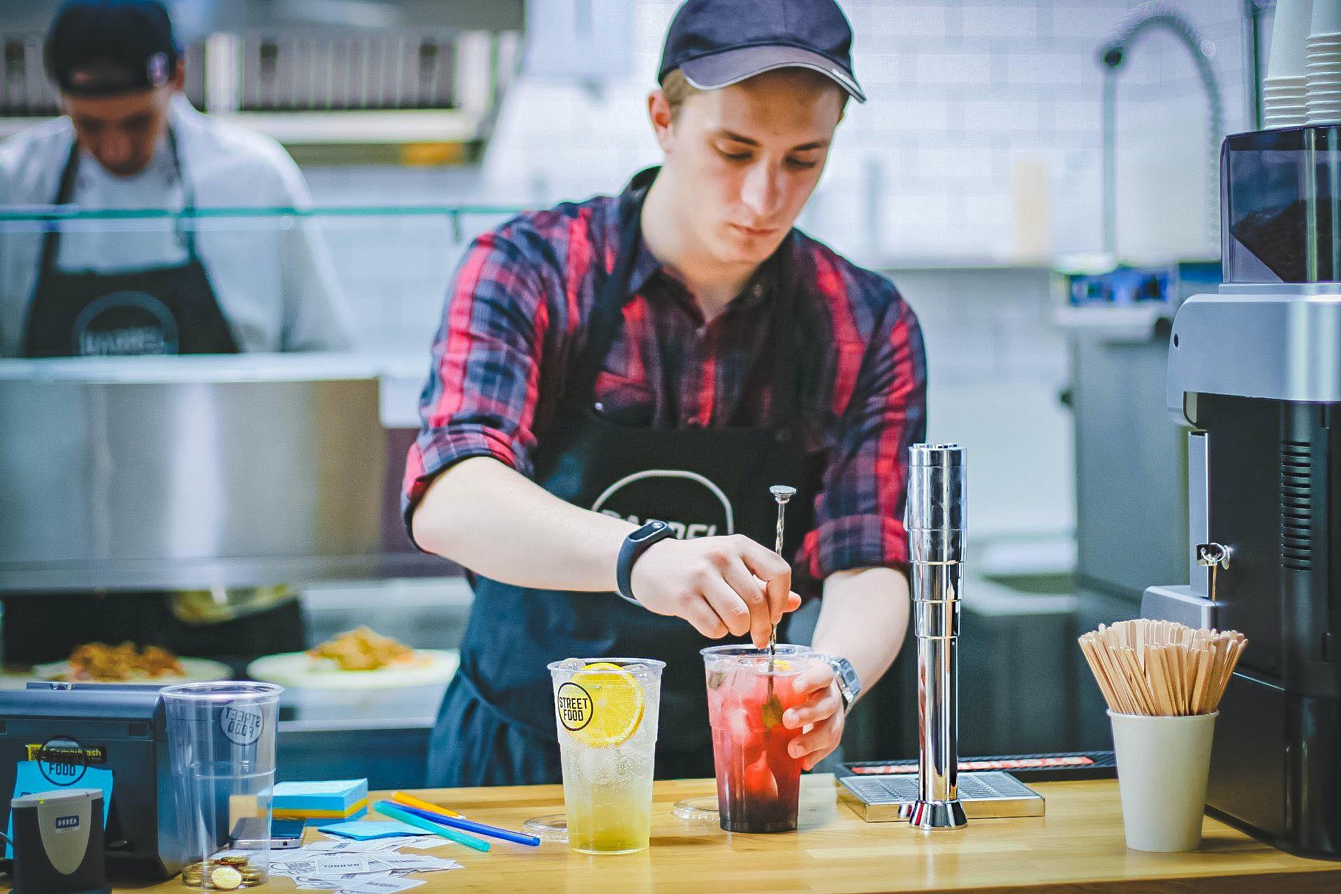 Man at work stirring drinks in a kitchen