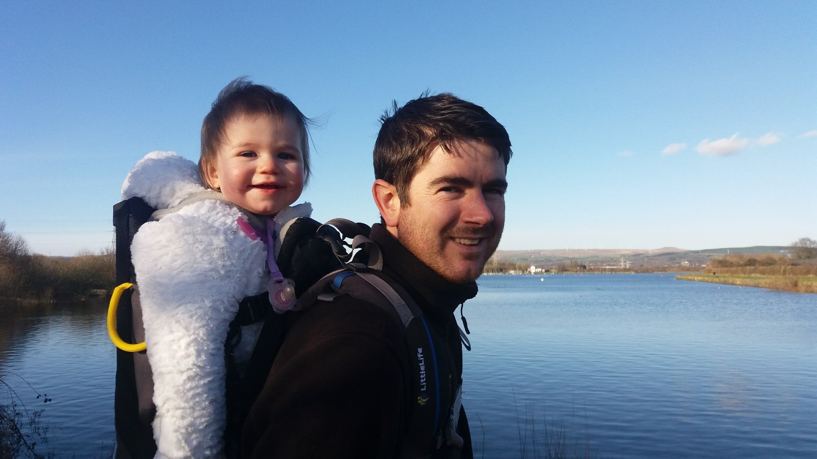 Father and child with Elton Reservoir in the background