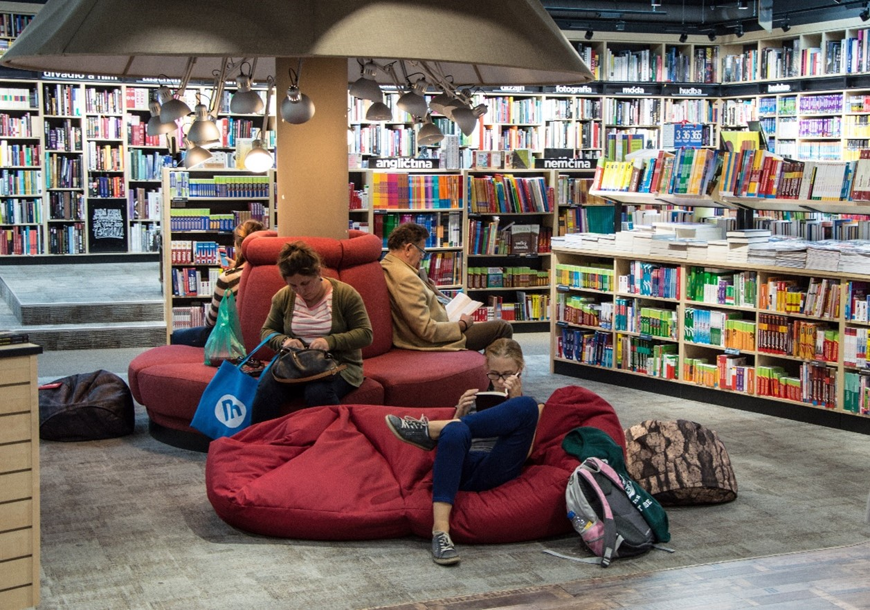 People sat on comfy chairs in a library reading books