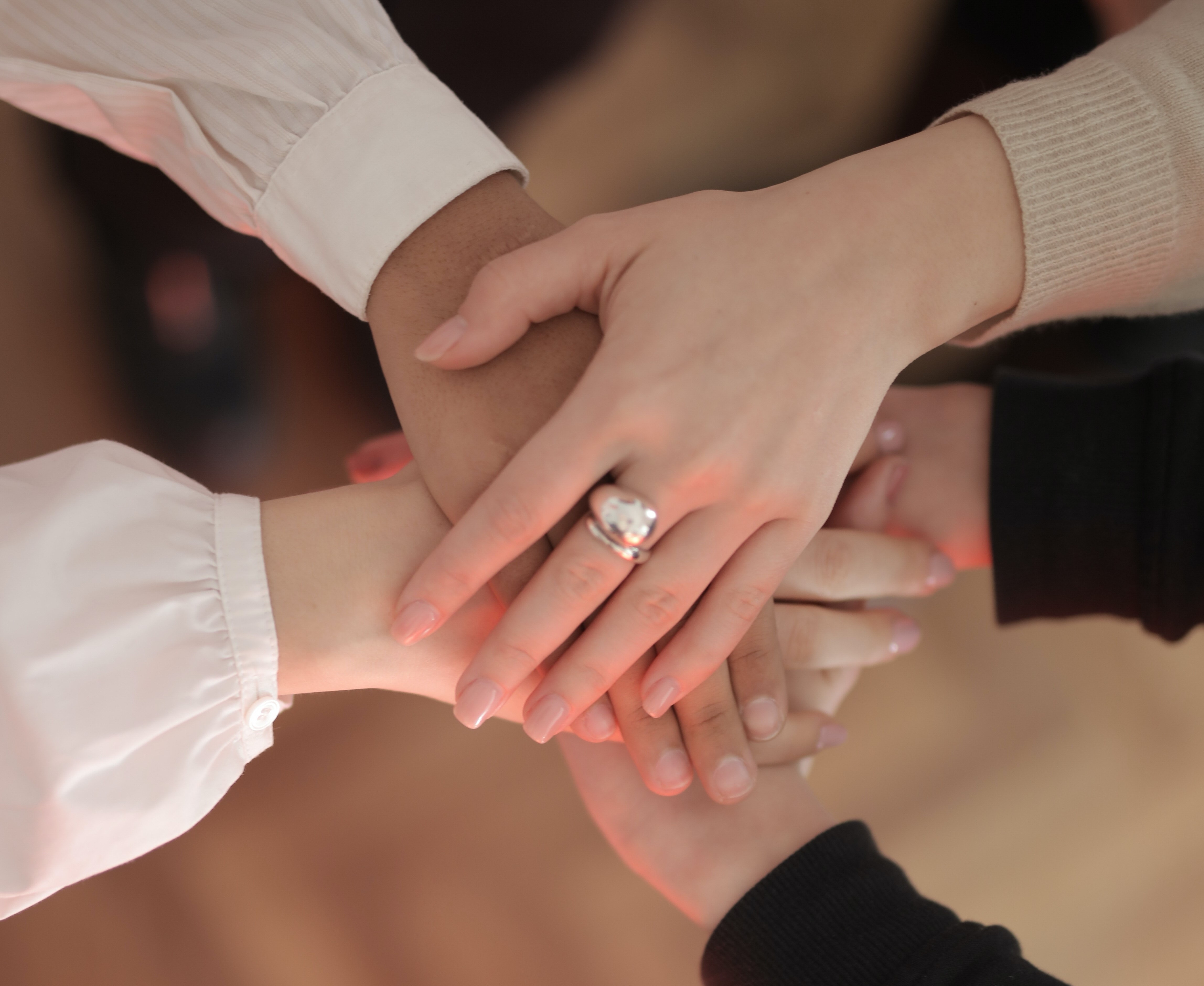 Four hands touching in the middle