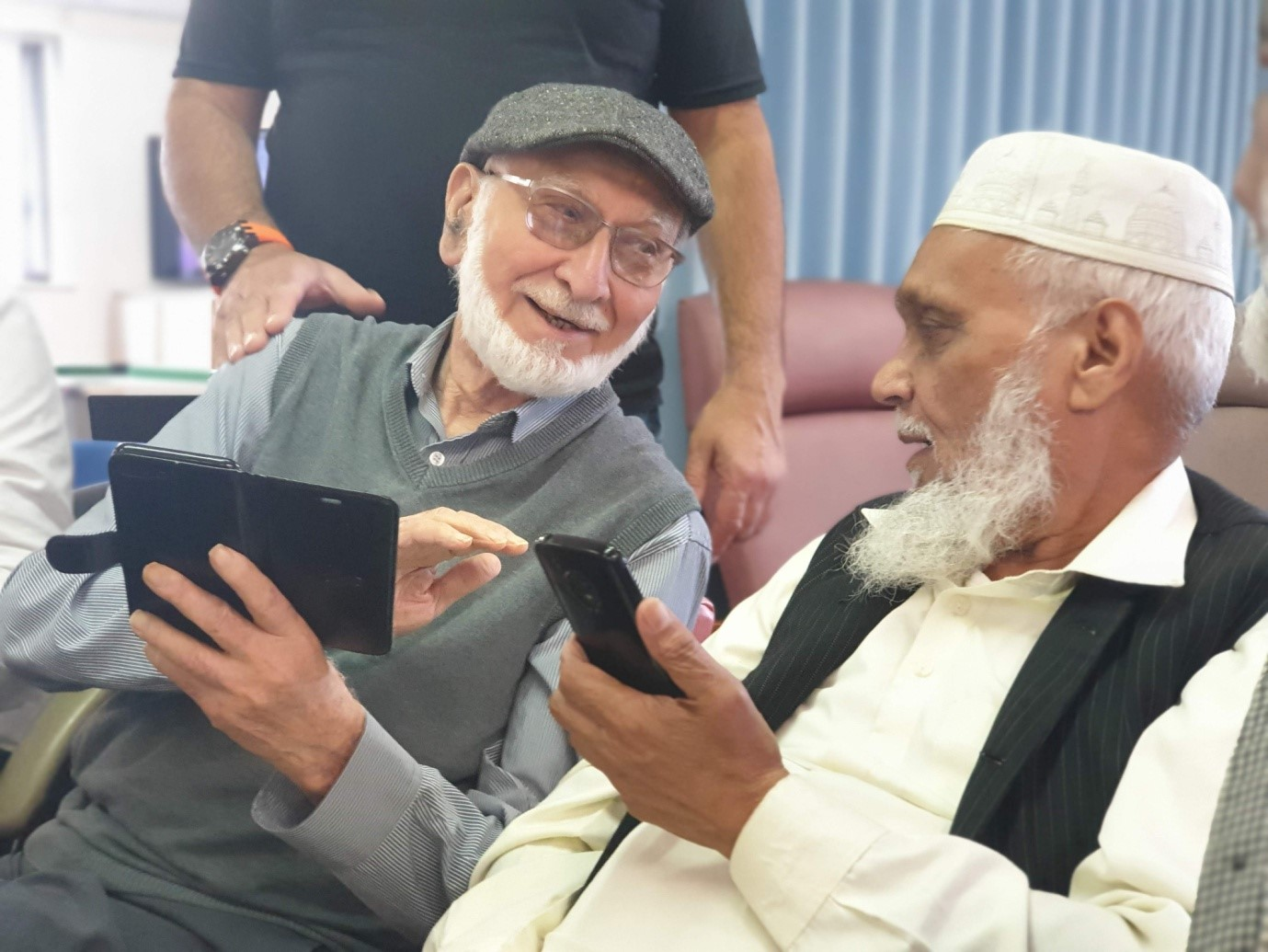 Two people in Jinnah Centre, chatting together and holding their phones